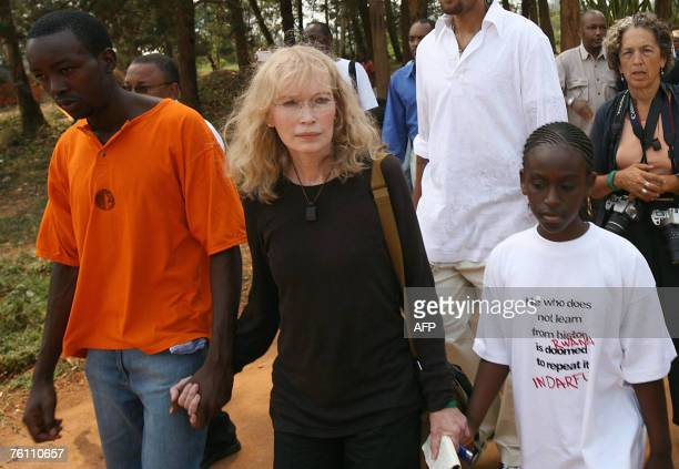 American actress Mia Farrow walks with Rwandan genocide survivors as they enter a mass grave in Kigali 15 August 2007 during a torch lighting...