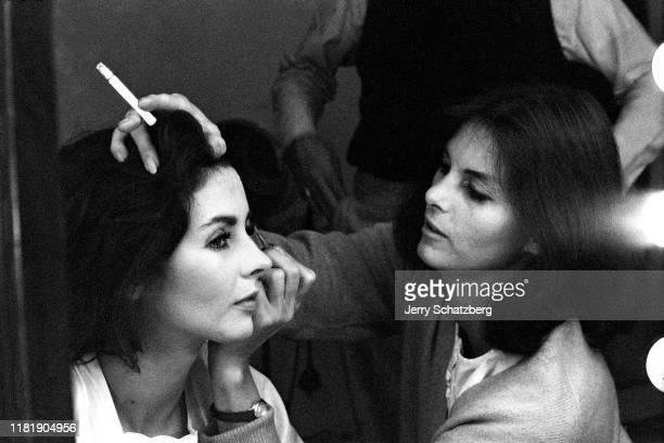 American actress Millie Perkins sits as model Anne St Marie a cigarette in one hand applies Perkin's eye makeup New York New York 1963