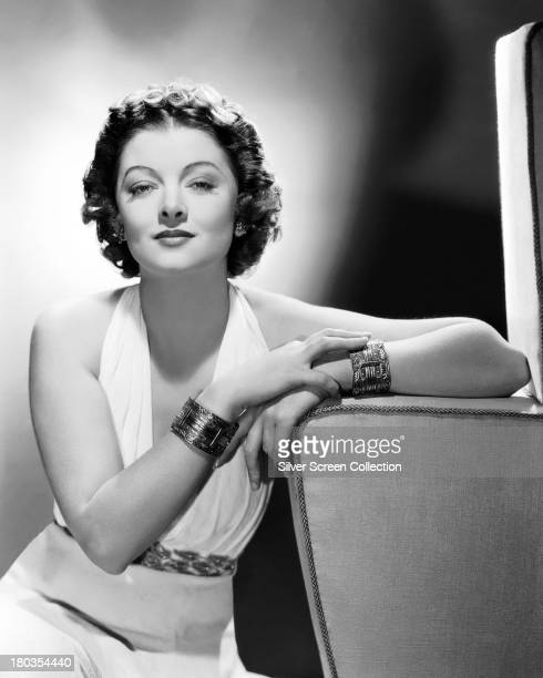 American actress Myrna Loy wearing a white evening dress and bracelets circa 1935