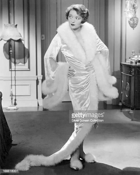 American actress Myrna Loy wearing a white furtrimmed satin robe and matching slippers circa 1935