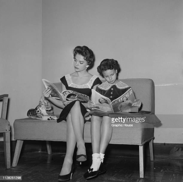 American actress Natalie Wood and he sister Lana Wood reading magazines in the dressing room of a clothes shop US 4th January 1956
