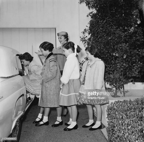 American actress Natalie Wood letting her sister Lana Wood and her friends entering a car, US, 6th January 1956.