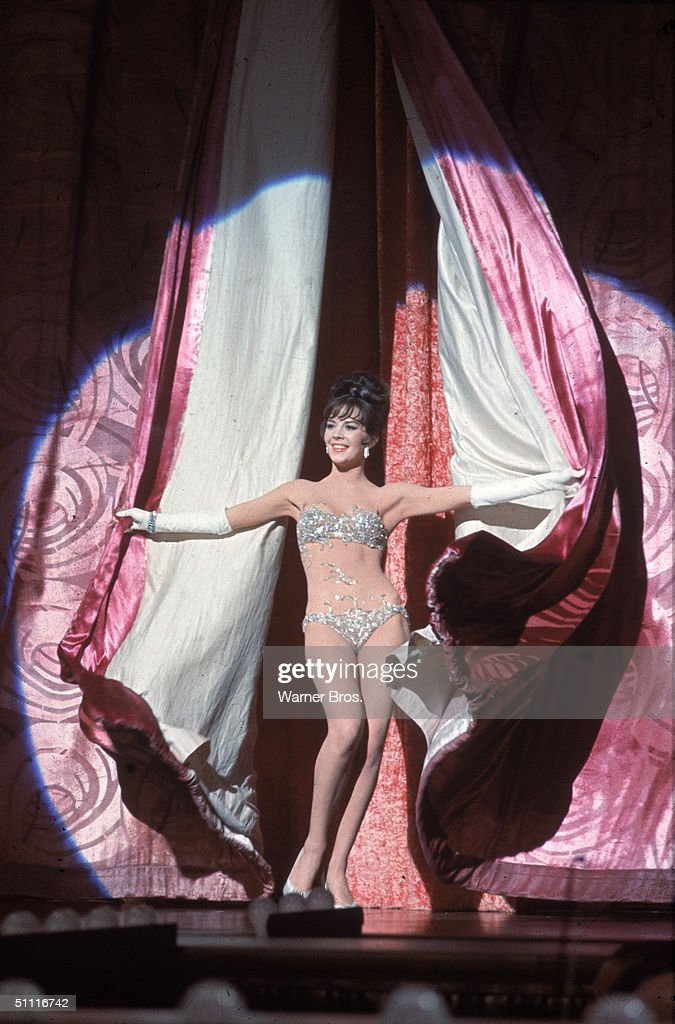 American actress Natalie Wood (1938 - 1981) throws back stage curtains as she performs as the burlesque stripper Gypsy Rose Lee in a publicity still from the movie 'Gypsy' directed by Mervyn LeRoy, 1962.