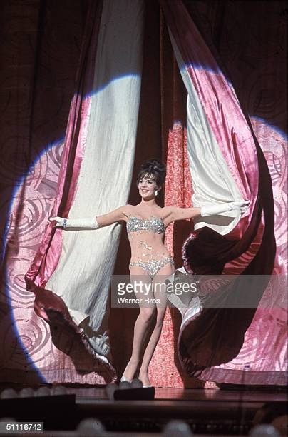 American actress Natalie Wood throws back stage curtains as she performs as the burlesque stripper Gypsy Rose Lee in a publicity still from the movie...