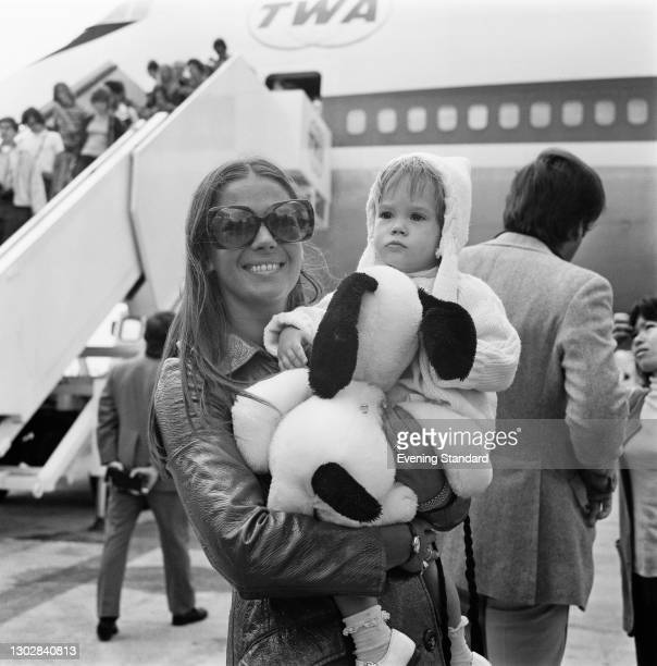 American actress Natalie Wood with her daughter Natasha at Heathrow Airport in London, UK, 4th August 1972. Natasha is holding a Snoopy toy.