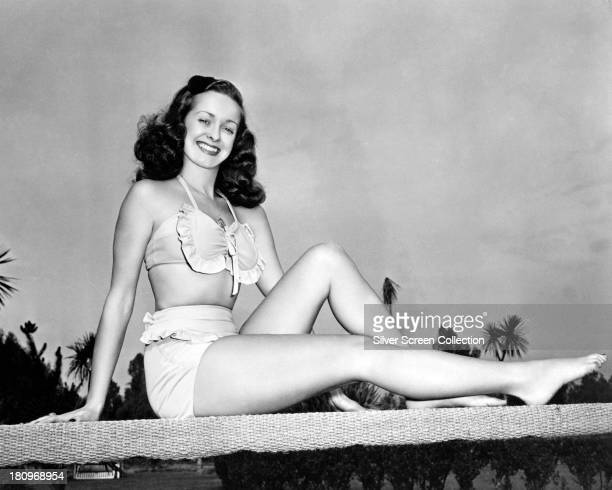 American actress Noel Neill sitting on a diving board in a two-piece, frilled bathing costume, circa 1945.