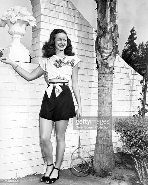 American actress Noel Neill wearing shorts and a floral print, sleeveless top, and holding a badminton racket, circa 1945.