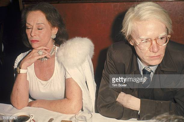 American actress Paulette Goddard and avantgarde artist Andy Warhol sit next to each other at a table at the opening party for the revival of the...
