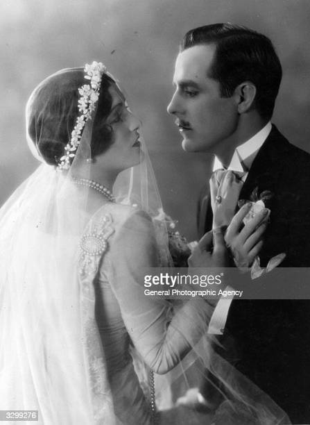 American actress Pauline Starke wearing a wedding dress and being embraced by Spanish romantic lead Antonio Moreno in the MGM film 'Love's Blindness'...
