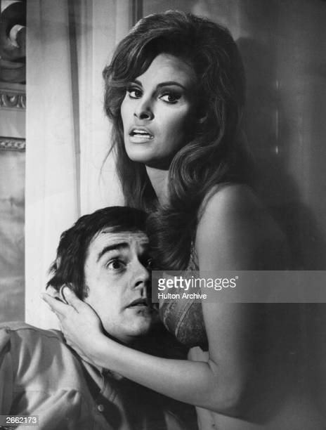American actress Raquel Welch clutching a bemused Dudley Moore to her bosom in a comic scene from the film 'Bedazzled'