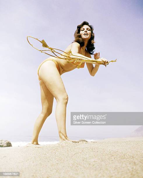 American actress Raquel Welch wearing a bikini on a beach, circa 1965. She is holding a strand of seaweed.