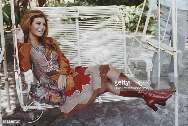 American actress Raquel Welch wearing a multicoloured suede patchwork skirt and jacket and leather boots sits on a swing seat in Rome Italy prior to...