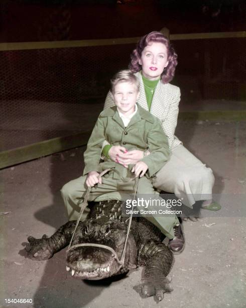 American actress Rhonda Fleming and a boy probably her son Kent Lane riding an alligator circa 1955