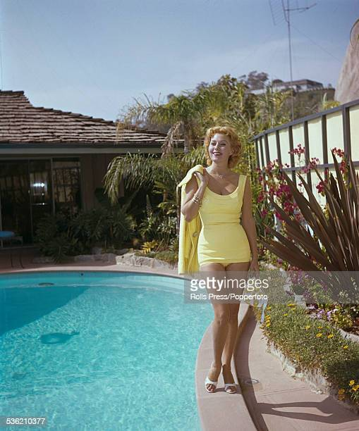 American actress Rhonda Fleming pictured wearing a lemon yellow swimsuit with matching jacket beside a domestic swimming pool in the United States...