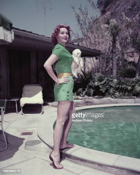 American actress Rhonda Fleming poses by a swimming pool with a small poodle circa 1955