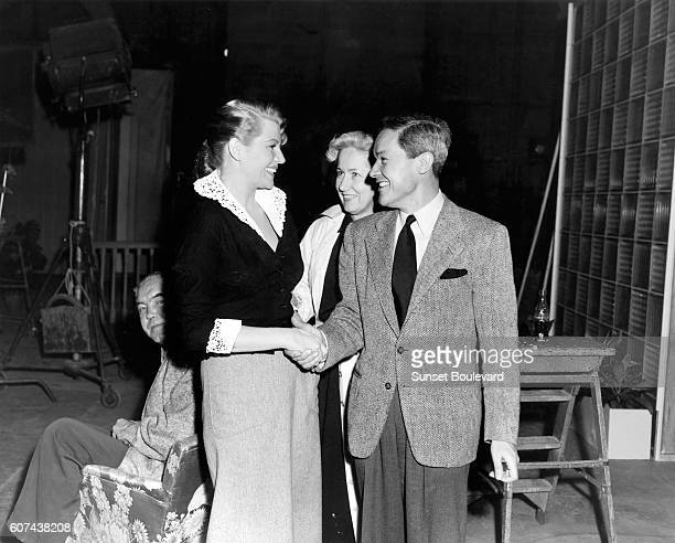 American actress Rita Hayworth greets French costume designer JeanLouis Berthault aka Jean Louis who designed her wardrobe from Columbia's 'Affair in...