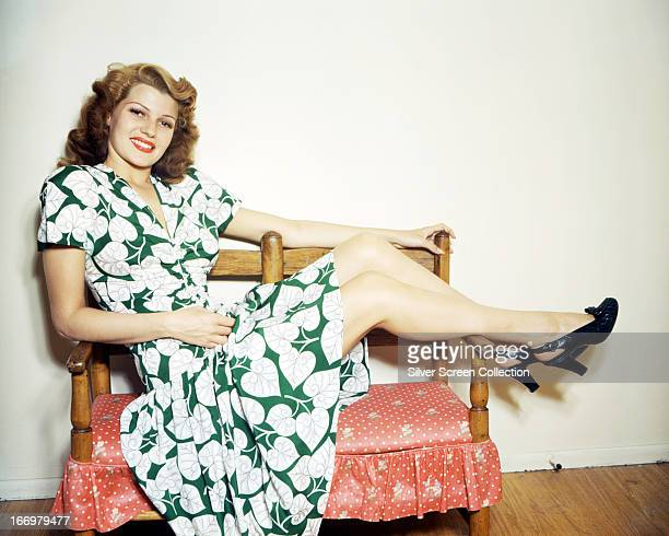 American actress Rita Hayworth wearing a green and white leafpatterned dress and putting her feet up circa 1945