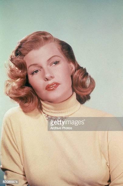 American actress Rita Hayworth wearing a yellow polo neck jersey, circa 1950.