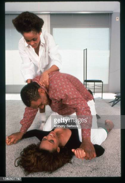 American actress Robin Givens smiles as her husband, heavyweight boxer Mike Tyson, pins her arms to the floor and her mother, Ruth, holds his...
