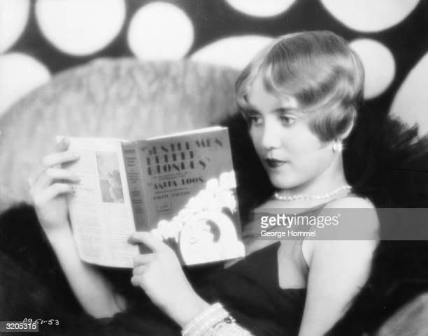 American actress Ruth Taylor reclines on a hair to read 'Gentlemen Prefer Blondes' by Anita Loos She played Lorelei Lee in the 1928 film of the same...