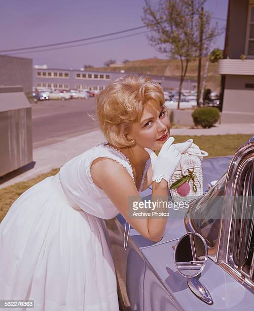 American actress Sandra Dee leaning on the hood of a car circa 1962