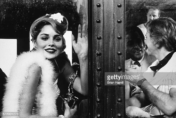 American actress Sharon Stone holds a trophy and waves on the set of the film 'Stardust Memories' 1980