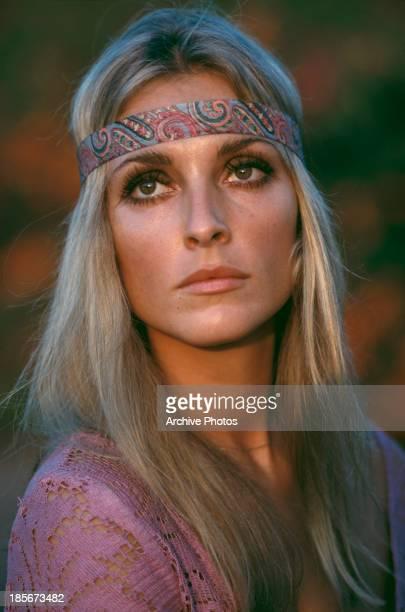 American actress Sharon Tate wearing a pink top and headband circa 1968