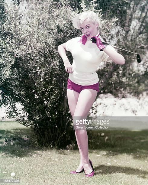 American actress Sheree North playing golf in pink shorts circa 1955