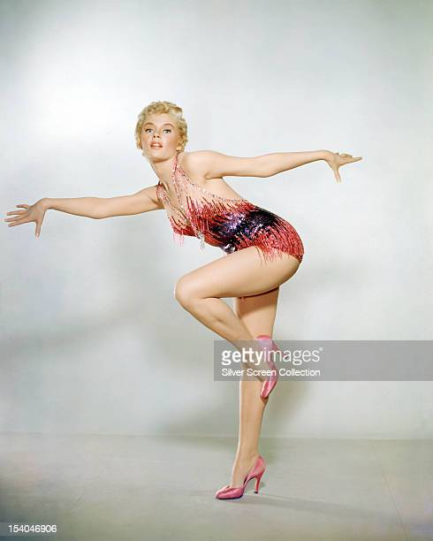 American actress Sheree North posing standing on one leg in a showgirl outfit and high heels circa 1955