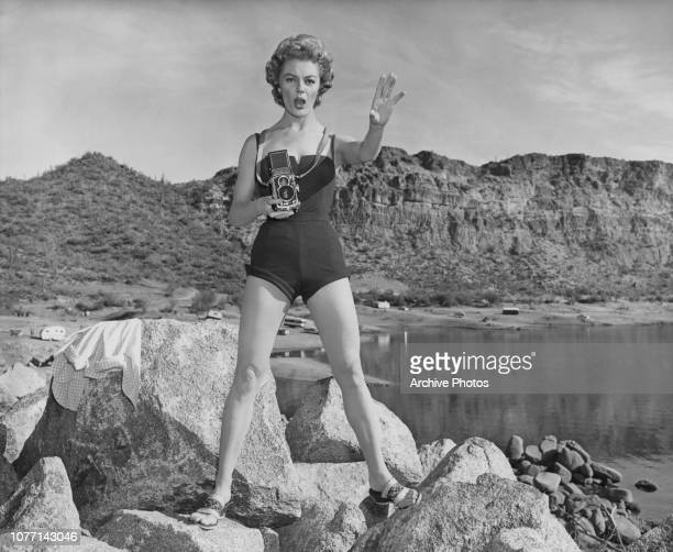 American actress Sheree North uses her Rolleiflex camera during the location filming of the 20th Century Fox production 'The Way to the Gold' at Lake...