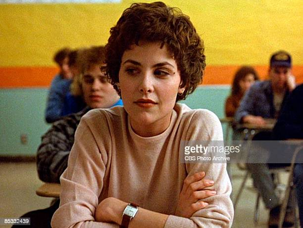 American actress Sherilyn Fenn sits in a classroom set with her arms crossed in a scene from the pilot episode of the television series 'Twin Peaks'...