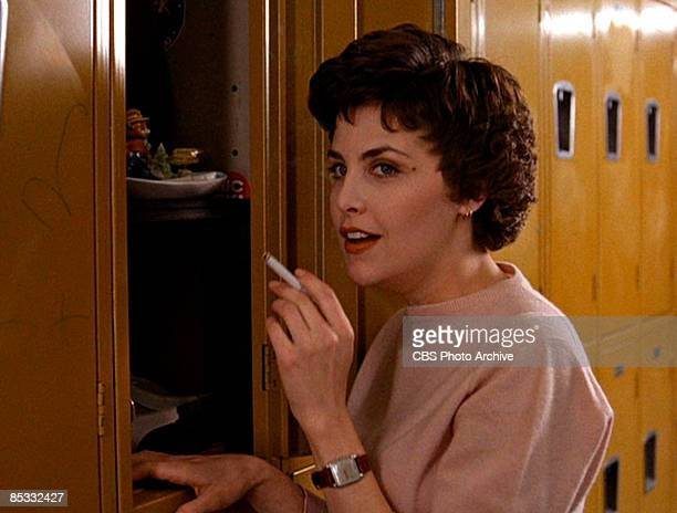 American actress Sherilyn Fenn smokes a cigarette at a locker in school hallway set in a scene from the pilot episode of the television series 'Twin...