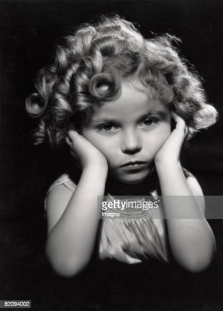 Academy Award winning actress tap dancer and iconic American child actress of the 1930s Shirley Temple holds her 1935 Academy Award the miniature...
