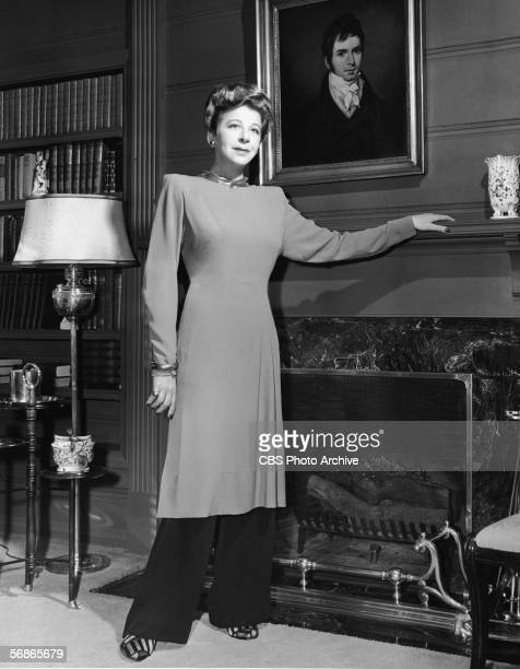 American actress singer and comedian Fanny Brice poses by a fireplace beneath a late 18th Century portrait in a cerise tunic over black trousers 1940s