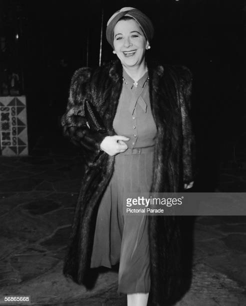 American actress singer and comedian Fanny Brice wears a turban and a fur coat as she arrives for a preview of the film 'The Cat and the Canary'...