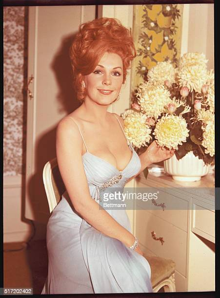 American actress Stella Stevens born in 1936 in Mississippi She is seated wearing a light blue lowcut dress pointing to a vase full of large yellow...
