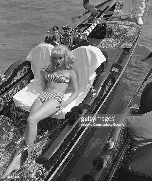 American actress Sue Lyon earing a strapless striped bikini and holding Lolita sunglasses portrayed while lying on a gondola Venice 1962