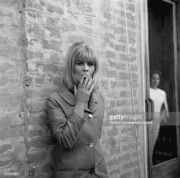 American actress Sue Lyon smoking a cigarette against a wall Venice 1973