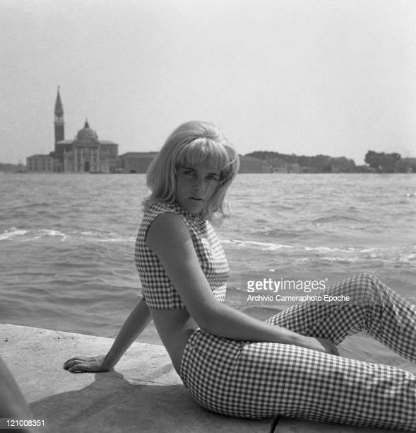 American actress Sue Lyon wearing vichy trousers and top portrayed while posing in front of San Giorgio Island Venice 1962