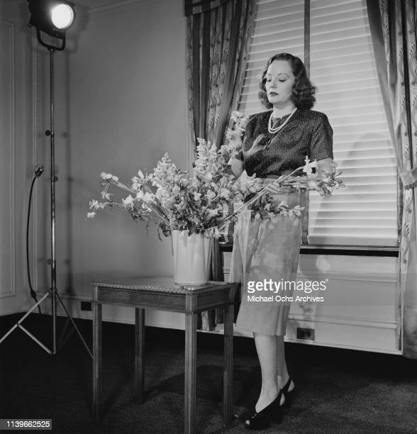 American actress Tallulah Bankhead arranges a bouquet of flowers in a vase in New York City 1947