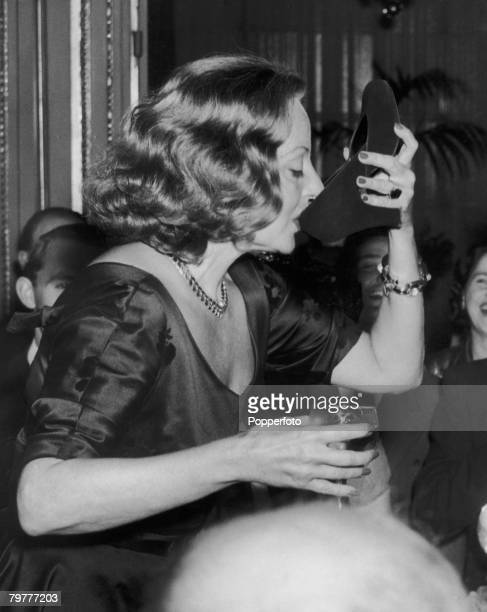 American actress Tallulah Bankhead drinks champagne from her shoe during a press conference at the Ritz Hotel in London 7th September 1951
