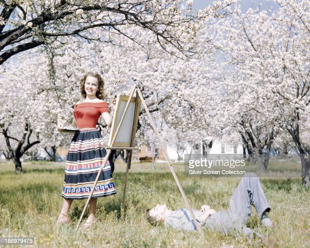 American actress Terry Moore painting in an orchard in spring blossom circa 1955