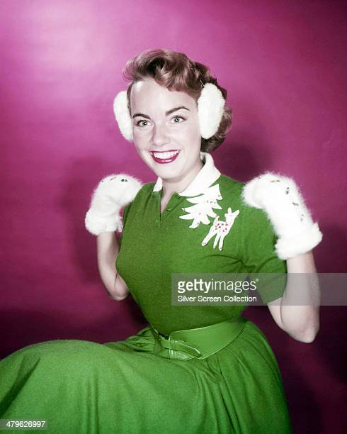 American actress Terry Moore wearing a green dress with Christmas motifs along with white mittens and nmatching ear muffs circa 1950