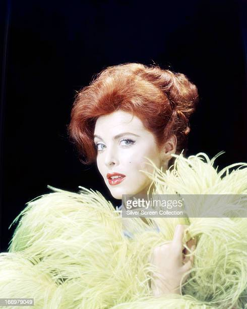 American actress Tina Louise posing with yellow ostrich feathers circa 1960