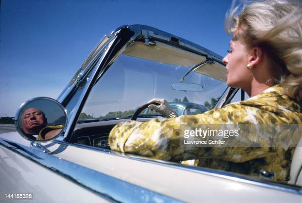 American actress Tippi Hedren drives a convertible on a freeway as Britishborn film director Alfred Hitchcock seated in the back seat is reflected in...