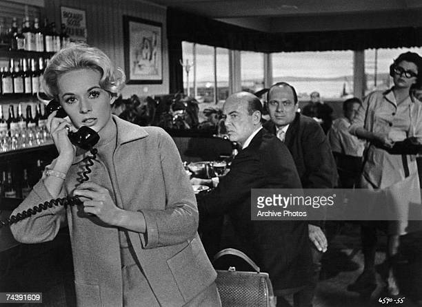 American actress Tippi Hedren makes a telephone call in a scene from 'The Birds' directed by Alfred Hitchcock for Universal 1963 Just behind her is...