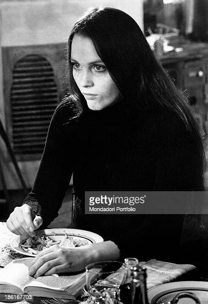 American actress Tisa Farrow, sister of American actress Mia Farrow , eating reading a book in the film And Hope to Die. Paris, 1972.
