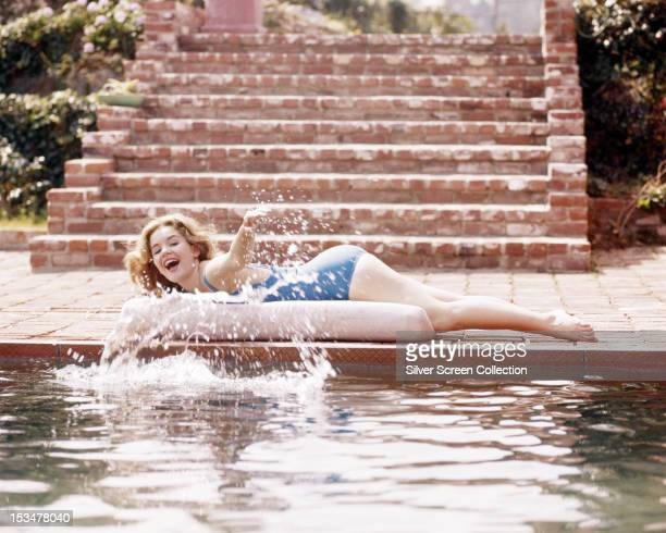 American actress Tuesday Weld lying by a swimming pool and splashing her hand in the water circa 1960