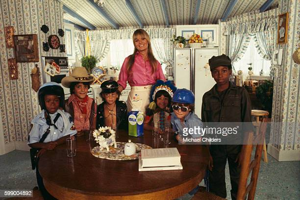 American actress Valerie Perrine surrounded by children dressed up as members of the disco band The Village People on the set of Can't Stop the Music...