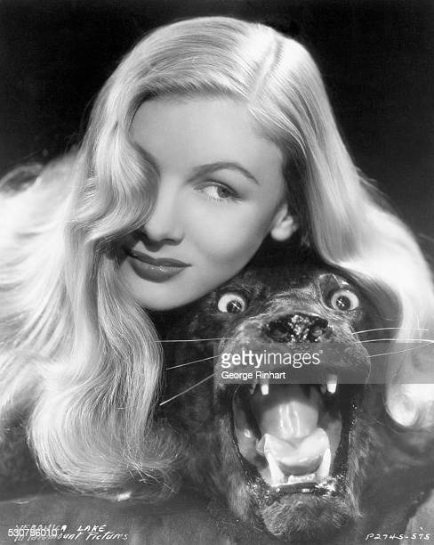 American actress Veronica Lake posing with the stuffed panther head from a panther skin rug Undated promotional photo for Paramount Pictures circa...